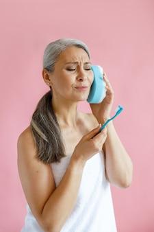 タオルに包まれた嫌な中年のアジアの女性は、スタジオでピンクの背景にバススポンジネラ耳を保持している歯ブラシを見ています。成熟した美容ライフスタイル