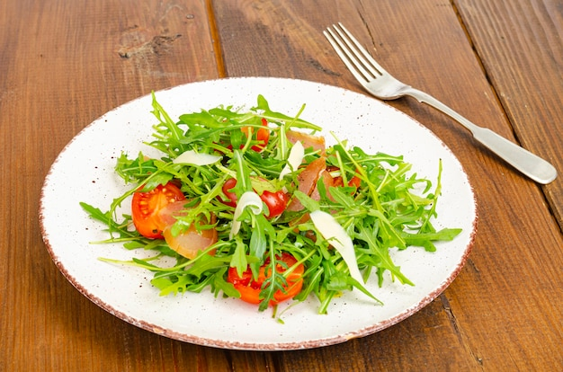 Dish of arugula, tomatoes, dried meat and cheese