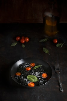 Dish of black spaghetti, with cherry tomatoes and basil, on a black wooden background