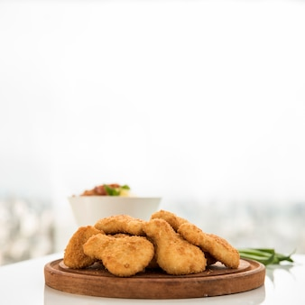 Dish of chicken pieces on serving board