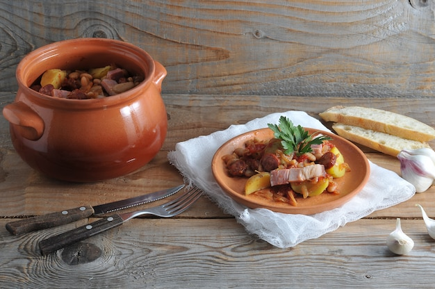 Dish cooked in a pot with potatoes, beans, smoked in a clay pot