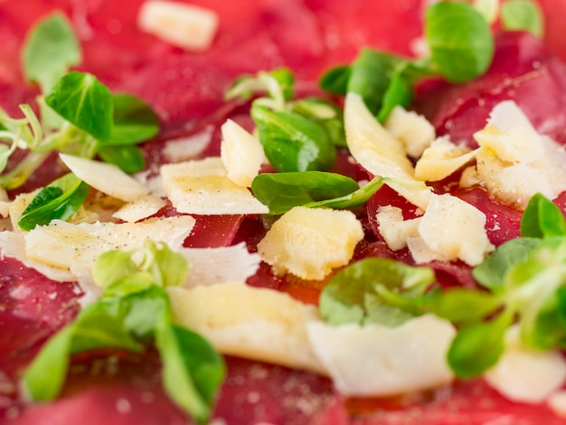 Dish of dried beef with parmesan and salad