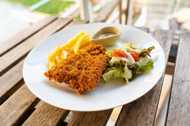 Блюдо рыба в кляре с картофелем фри. рыба на тарелку с картофелем и салатом в летнем кафе.
