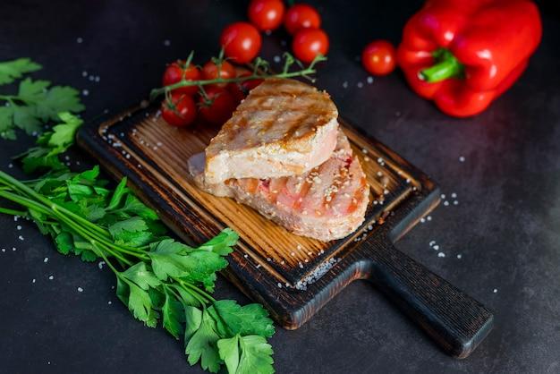 Блюдо рыбный стейк из тунца на гриле с овощами на тарелке в ресторане