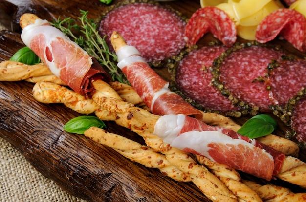 前菜のおやつ用ディッシュ木の表面にサラミを添えた生ハムで包んだグリッシーニ