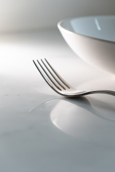 Dish and fork on white marble texture background. concept for food and dining tableware