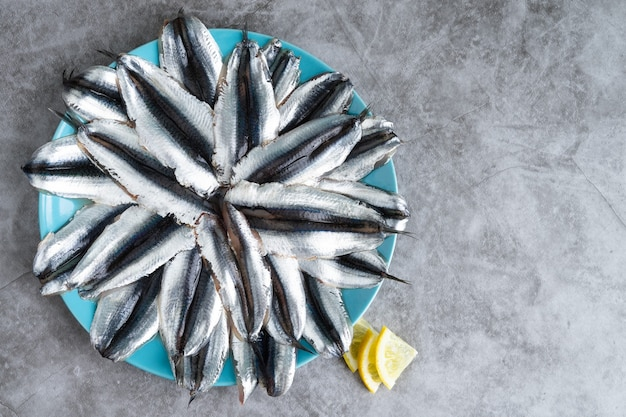 Dish full of anchovies on marble bottom. copy space.