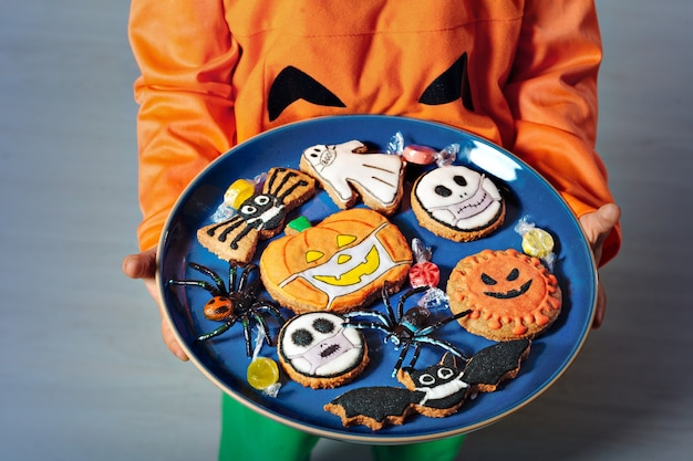 A dish in the hands of a child with original decorated gingerbread cookies for halloween