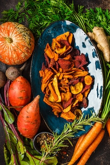 Dish of healthy vegetable chips from beets, sweet potatoes, pumpkin and carrots with ingredients on dark table.