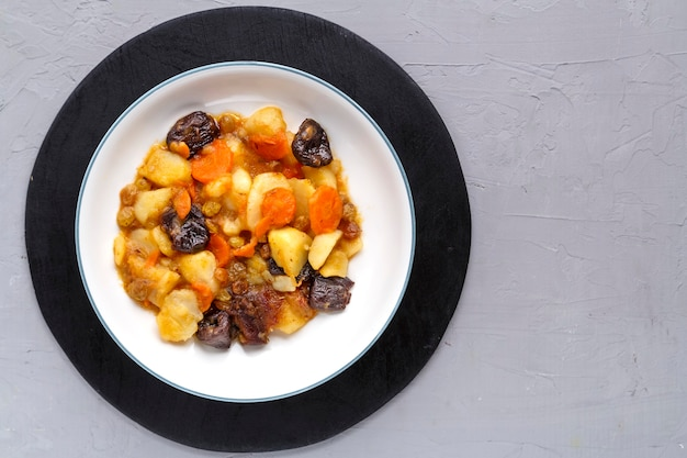 A dish of jewish cuisine sweet tsimes with carrots and dates vegetarian in a plate on a round stand on a concrete surface