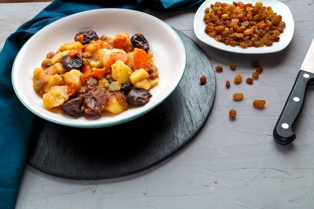 A dish of jewish cuisine sweet tsimes with carrots vegetarian dates in a plate on a round stand on a concrete surface next to raisins on a saucer