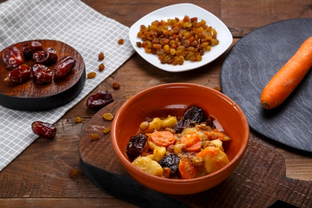 A dish of jewish cuisine sweet tsimes with carrots with dates in a plate next to a spoon and carrots with dried fruits