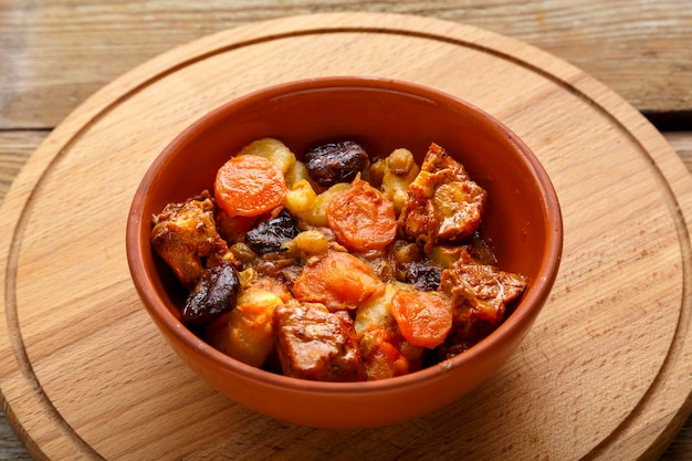 A dish of jewish cuisine tsimes with carrots, dates and turkey meat in a clay plate on a wooden round stand
