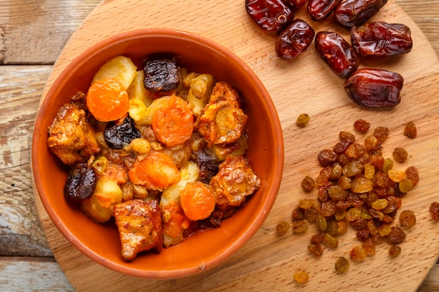 A dish of jewish cuisine tsimes with carrots, dates and turkey meat in a plate on a wooden surface next to raisins and dates sprinkled