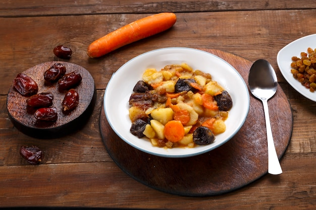 A dish of jewish cuisine - tsimes with carrots and dates in a white plate on a round stand next to a spoon and carrots with dried fruits