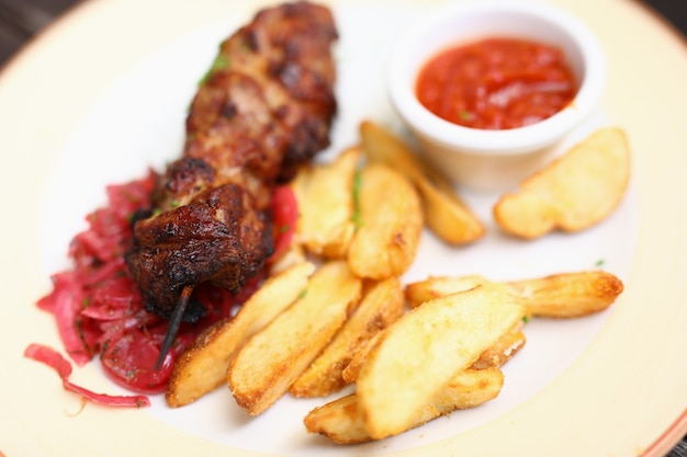 Dish of kebabs on skewer of potatoes and salad with sauce