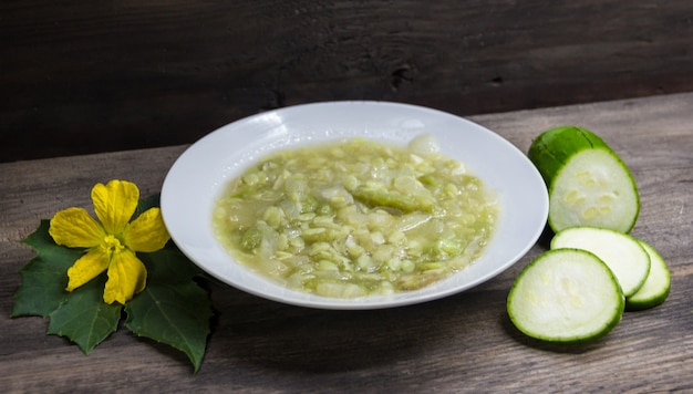 Dish of luffa with garlic and onion on wooden background
