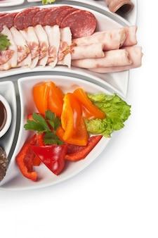 各種ソーセージと白で隔離される野菜の料理