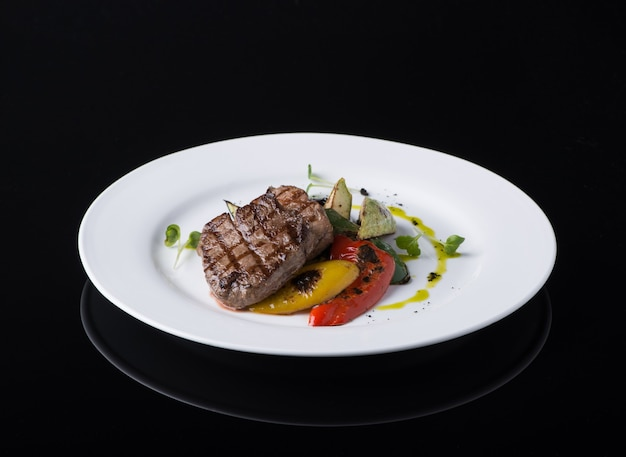 Блюдо из жареного мяса в тарелке на черном фоне