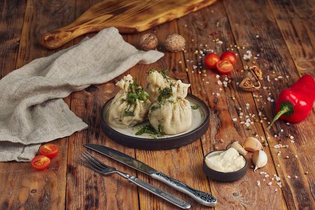 Блюдо грузинской кухни хинкали в красивой тарелке на деревянном столе