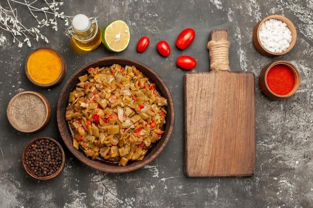 まな板の隣のボウルにサヤインゲンの皿オイルのカラフルなスパイスとトマトのサヤインゲンの皿