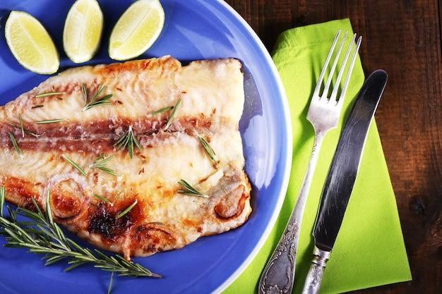 木製のテーブルにローズマリーとライムとパンガシウスの切り身の料理