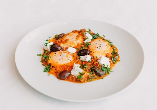 白いプレートの上面図でオリーブとフェタチーズと3つの卵からスクランブルエッグの料理