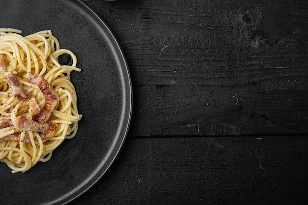 Блюдо из спагетти карбонара, современный итальянский рецепт пасты с гуанчиале, набор яиц и сыра пекорино романо, на черном деревянном столе, плоская планировка, вид сверху, с копией пространства