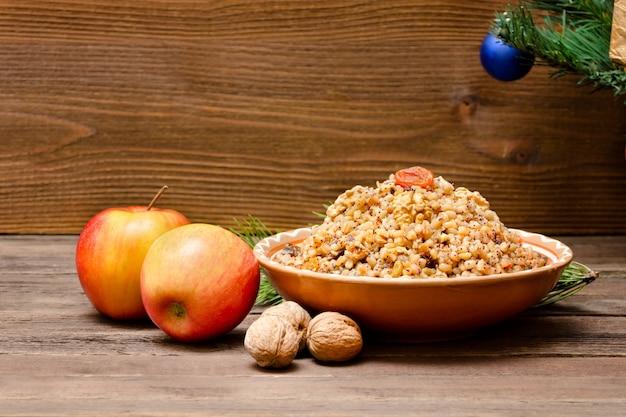 クリスマスイブの伝統的なスラブ料理の料理。クリスマスツリー、リンゴ、クルミ。茶色の木製の背景。コピースペース