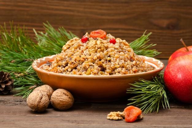 茶色の木製テーブルの上のクリスマスイブの伝統的なスラブ料理の料理。松の枝、リンゴ、クルミ。閉じる