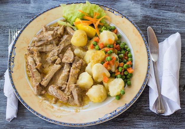 ジャガイモ豆の肉と緑の野菜とカトラリー食器の皿皿