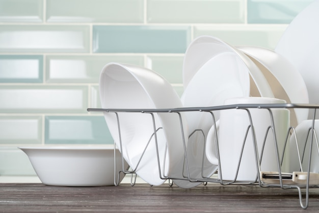 Dish rack with clean dry dishes on kitchen counter