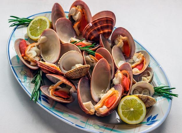 Dish of vivid fresh seafood with lemon and rosemary.