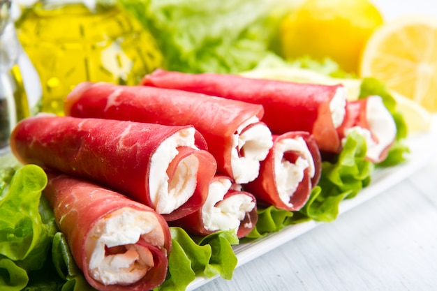 Dish with bresaola and cheese rolls with salad