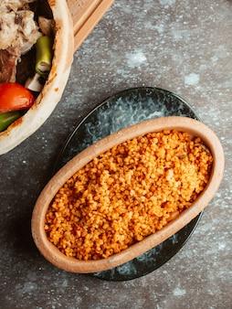Dish with bulgur with tomato sauce