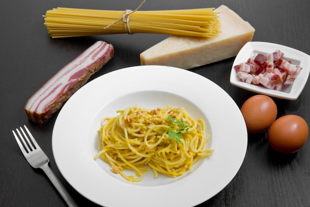 Dish with carbonara's spaghetti and ingredients