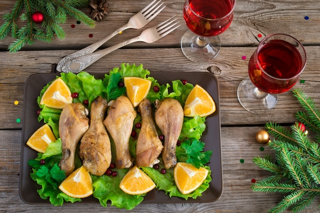 Dish with chicken legs, salad, orange and cranberries.