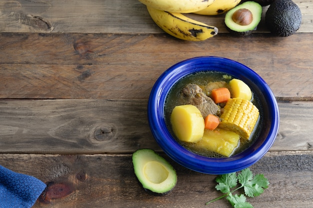 Dish with colombian sancocho on wooden background with decoration. copy space.