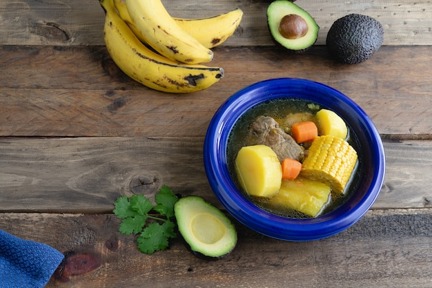 Dish with colombian sancocho on wooden surface with decoration. copy space.