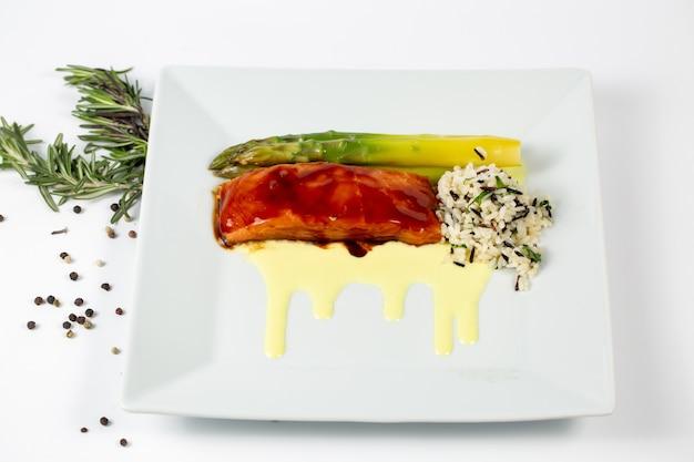 Блюдо со свежей рыбой, спаржей и рисом на тарелке