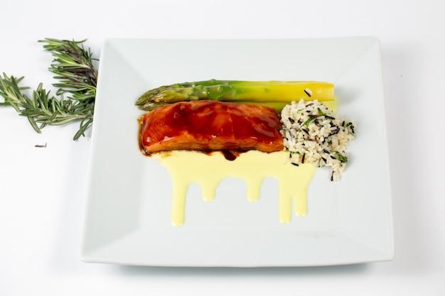 新鮮な魚のアスパラガスとご飯を皿に盛り付けた料理