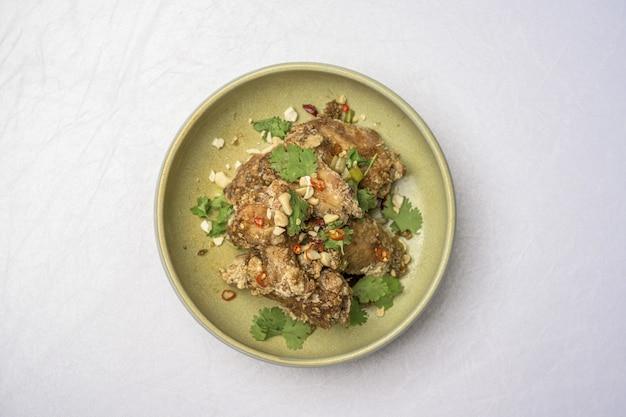 白いテーブルの上の緑のプレートでフライドチキンと料理