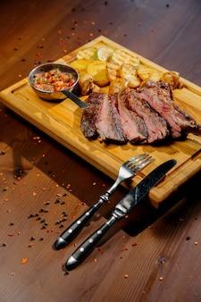 木製テーブルの上の皿に肉とフライドポテトを料理します。トップビュー