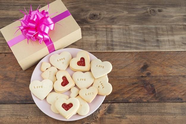 Блюдо с печеньем в форме сердца на деревянной основе. концепция день святого валентина