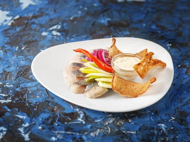 Блюдо с селедкой на белой тарелке.
