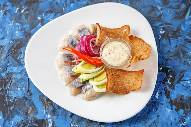 Dish with herring on a white plate. top view. the concept of foo