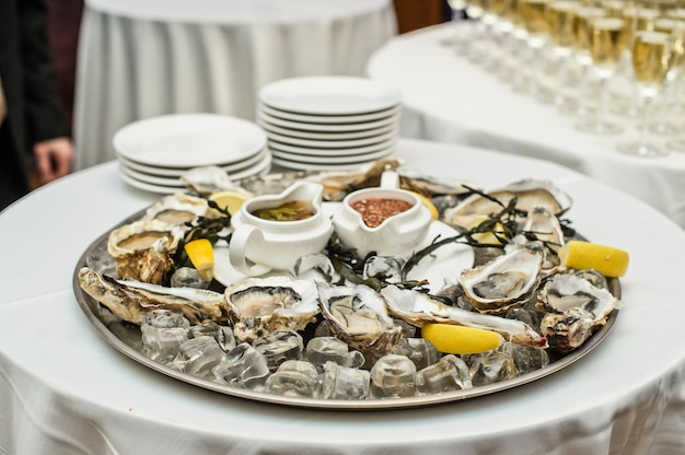 Dish with live oysters on the table in the interior of a luxury restaurant