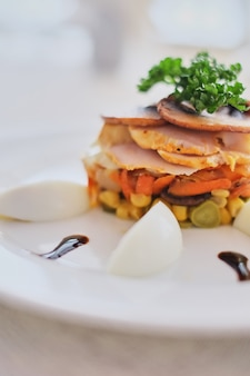 Dish with mushrooms ham carrots and corn with eggs white background in cafe