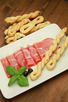 Dish with raw ham and breadstick