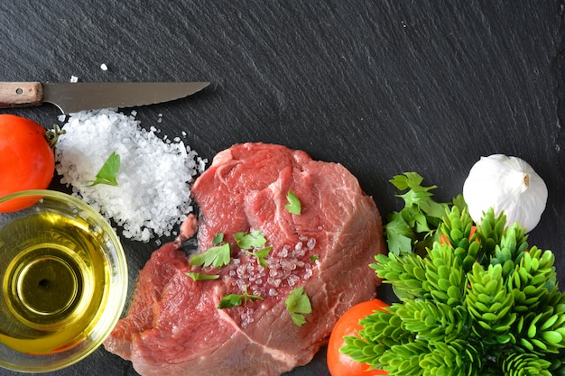 Dish with raw meat with salt, oil and parsley